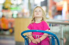 Adorble baby sit on shopping cart in mall Stock Photo