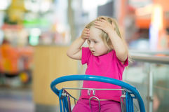 Adorble baby sit on shopping cart in mall Stock Image