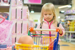 Adorble girl with small shopping cart in kids mall Royalty Free Stock Photography