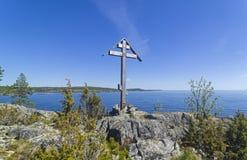 Adore la cruz en una roca en la orilla del lago ladoga fotografía de archivo libre de regalías