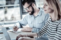 Satisfied unshaken man sitting and writing. Adore my work. Satisfied unshaken busy men sitting in the office by the table near his colleague smiling and writing Royalty Free Stock Image