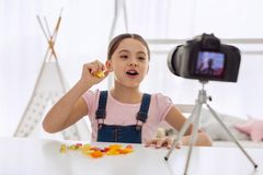 Upbeat girl speaking about taste of gummy candies in vlog. Adore the taste. Cheerful pre-teen girl sitting at the table and speaking about the taste of gummy Royalty Free Stock Photo