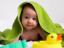 Adoreble baby girl in towel looking at duckling and sponge Royalty Free Stock Images
