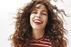 Adorez-moi Portrait de femme adulte chaude insouciante avec les cheveux bouclés qui flottent en air, souriant largement et regard photo libre de droits