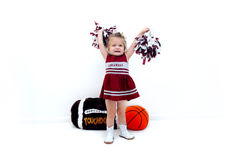Adoring Arkansas Fan. Little cheerleader dressed in burgundy and grey holds pom poms high in the air.  She is wearing white gogo boots and standing in front of a Royalty Free Stock Images