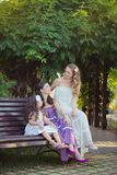 Adoring Brunette blond chestnut blue eyes sisters girls wearing cosy night white purple dress enjoying lifetime together summer su. Nny day in garden forest Stock Image