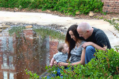 Adoring parents. Baby is fascinated with his parent's communication and interaction.  He gazes mesmerized into his parent's faces as they kneel besides a pool in Royalty Free Stock Images
