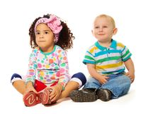 Adoring two years old couple. Black girl and Caucasian boy sitting together on the white background Royalty Free Stock Photography