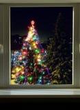 Adornó el árbol de navidad grande fuera de la ventana Foto de archivo libre de regalías