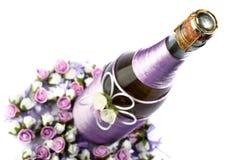 Adornado casandose la botella de champán con las rosas, aislada Imagen de archivo libre de regalías
