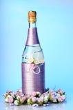 Adornado casandose la botella de champán con las rosas aisladas Foto de archivo libre de regalías