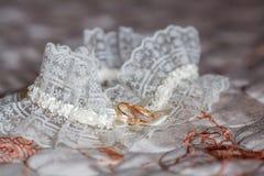 Adornado casandose la liga con dos anillos de oro concepto de la boda Imágenes de archivo libres de regalías