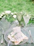 Adornado casandose la tabla con la composición hermosa de la flor, el vidrio para el vino y la placa, al aire libre, bella arte Fotos de archivo libres de regalías