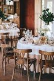 Adornado casandose la tabla en el estilo rústico para la cena con los manteles blancos y beige, copas de vino para las flores y Imagen de archivo