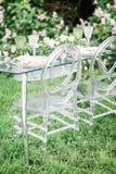 Adornado casandose la tabla para dos con la composición hermosa de la flor de las flores, vidrios para el vino, al aire libre, be Imagenes de archivo