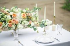 Adornado casandose la tabla para dos con la composición hermosa de la flor, los vidrios para el vino, las velas y las placas, al  Imagenes de archivo
