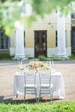Adornado casandose la tabla para dos con la composición hermosa de la flor, los vidrios para el vino, las velas y las placas, al  Imagen de archivo libre de regalías