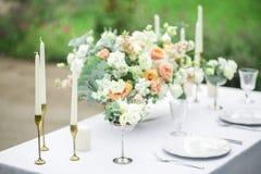 Adornado casandose la tabla para dos con la composición hermosa de la flor, los vidrios para el vino, las velas y las placas, al  Fotografía de archivo libre de regalías