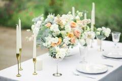 Adornado casandose la tabla para dos con la composición hermosa de la flor, los vidrios para el vino, las velas y las placas, al  Imagen de archivo