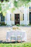Adornado casandose la tabla para dos con la composición hermosa de la flor, los vidrios para el vino, las velas y las placas, al  Fotografía de archivo