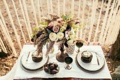 Adornado casandose la tabla para dos con un paño adornado con la composición floral de la lila florece en un fondo del lugar de l Fotos de archivo libres de regalías