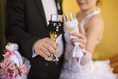 Adornado casandose los vidrios en las manos de la novia y del novio Imagen de archivo