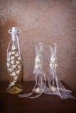 Adornado casandose los vidrios y la botella de champán Fotos de archivo libres de regalías