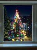 Adornado con el árbol de navidad grande de las guirnaldas de la Navidad fuera de la ventana Fotos de archivo