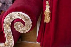 Adornado con el estilo clásico del oro del sofá en rojo Fotografía de archivo libre de regalías