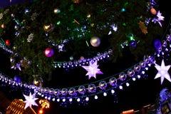 Adornado con el ligh de las chucherías y del árbol de navidad y de la ciudad de las guirnaldas Fotos de archivo libres de regalías