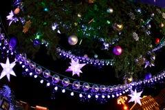 Adornado con el ligh de las chucherías y del árbol de navidad y de la ciudad de las guirnaldas Foto de archivo