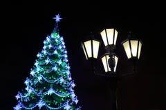 Adornado con el ligh de las chucherías y del árbol de navidad y de la ciudad de las guirnaldas Fotografía de archivo