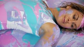 Adornado con la muchacha de la yoga de la pintura que pone en ella detrás en la pintura almacen de metraje de vídeo
