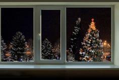Adornado con las guirnaldas del árbol de navidad fuera de la ventana Imágenes de archivo libres de regalías