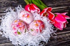 Adornado con los huevos y las flores pintados de Pascua en un fondo de madera Imagen de archivo libre de regalías