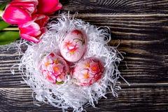 Adornado con los huevos y las flores pintados de Pascua en un fondo de madera Imagenes de archivo