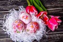 Adornado con los huevos y las flores pintados de Pascua en un fondo de madera Fotos de archivo libres de regalías
