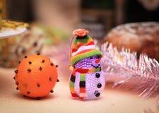 Adornado con una naranja y un muñeco de nieve del juguete en la tabla de la Navidad Fotografía de archivo libre de regalías