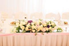 Adornado elegante con las flores blancas, los vidrios y las velas de restaurante para celebrar la boda Foto de archivo