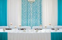 Adornado maravillosamente casandose la novia y al novio de la tabla en un restaur Imagenes de archivo