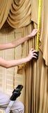 Adornamiento casero, mujer que mide para las nuevas cortinas con el golpecito del metal Fotos de archivo