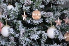 Adornamiento de ascendente cercano del árbol de navidad Bulbo de la decoración, árbol de abeto verde nevoso, juguetes rosados de  Fotos de archivo libres de regalías