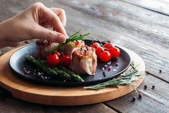 Adornamiento de la comida Cocinero que adorna un plato del cerdo Fotos de archivo libres de regalías