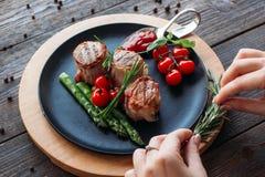 Adornamiento de la comida Cocinero que adorna un plato del cerdo Imagenes de archivo