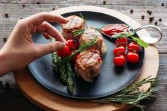 Adornamiento de la comida Cocinero que adorna un plato del cerdo Foto de archivo libre de regalías