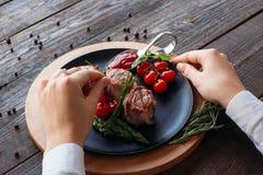Adornamiento de la comida Cocinero que adorna un plato del cerdo Fotos de archivo