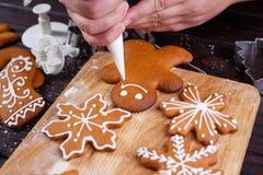 Adornamiento de la panadería de la Navidad Manos de la mujer que adornan la ginebra hecha en casa Fotografía de archivo libre de regalías