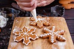 Adornamiento de la panadería de la Navidad Manos de la mujer que adornan la ginebra hecha en casa Imagen de archivo