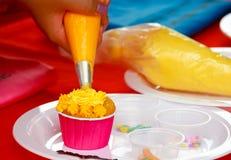 Adornamiento de la torta: ciérrese para arriba de la mano de la mujer joven con la creatina azotada Fotografía de archivo
