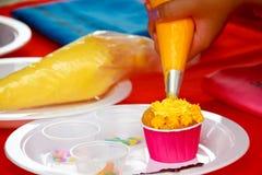 Adornamiento de la torta: ciérrese para arriba de la mano de la mujer joven con la creatina azotada Imagen de archivo